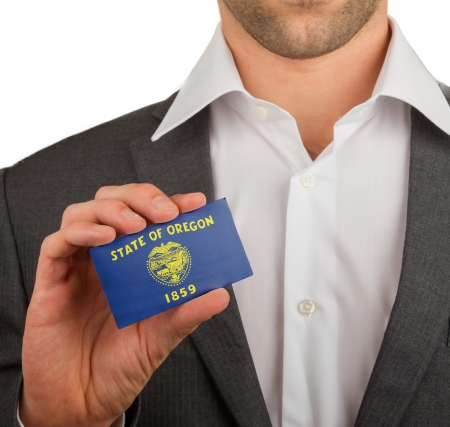 Businessman is holding a business card, flag of Oregon
