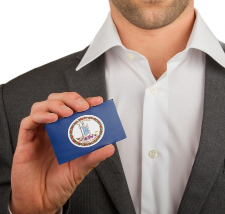 Businessman is holding a business card, flag of Virginia photo
