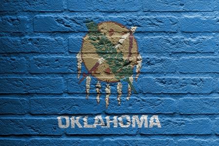 Mur de briques avec une peinture d'un drapeau, isolé Oklahoma