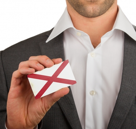 Businessman is holding a business card, flag of Alabama