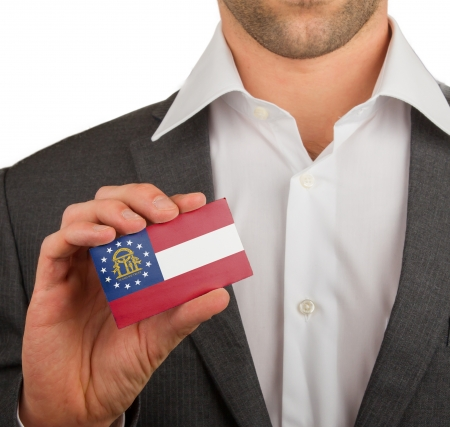 patiotic: Businessman is holding a business card, flag of Georgia