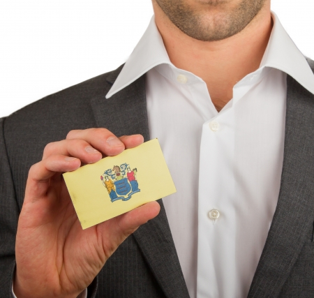 patiotic: Businessman is holding a business card, flag of New Jersey