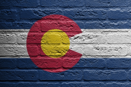 brick and mortar: Brick wall with a painting of a flag isolated, Colorado