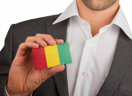 Businessman is holding a business card, flag of Guinea Stock Photo - 18213472