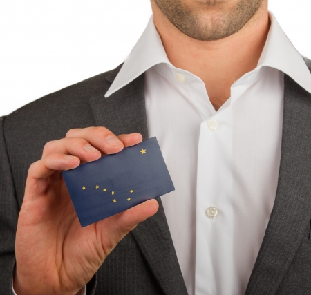 patiotic: Businessman is holding a business card, flag of Alaska