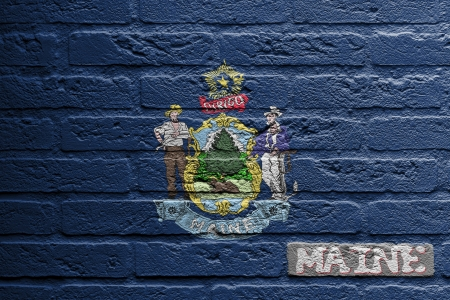 Brick wall with a painting of a flag isolated, Maine photo