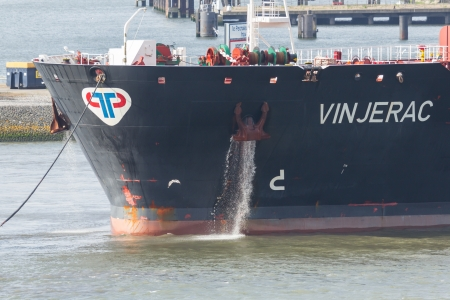 ROTTERDAM, THE NETHERLANDS - JUNE 22: Bow of the oil tanker with anchor and leaking sea water in the busy port of Rotterdam, Rotterdam, June 22, 2012
