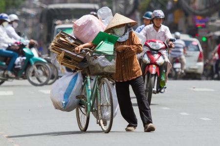 wheater: HUE, VIETNAM - JULY 25. Vietnamese woman packed her possesions on a bicycle and is fleeing for the coming Typhoon Vicente on July 25, Hue, Vietnam