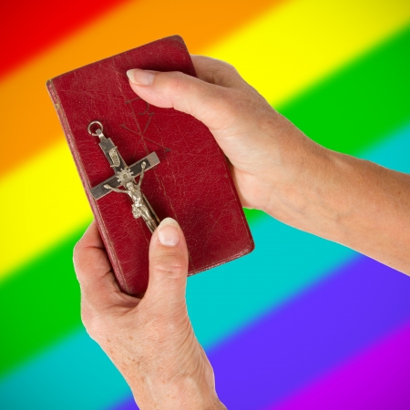 jezus: Old hands (woman) holding a very old bible, rainbow flag pattern