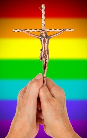jezus: Old woman holding a brass catholic crucifix, isolated on white, rainbow flag pattern