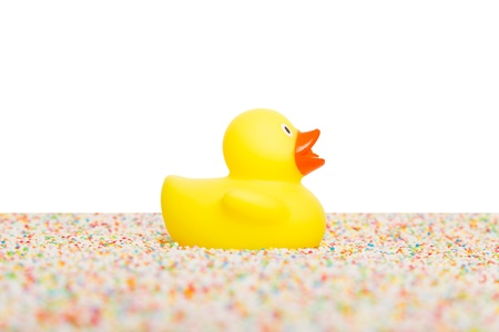 squeaky clean: Rubber duck isolated, sitting on colorful candy