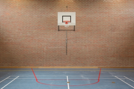 gym room: Interior of a gym at school, jumping high at the basket Stock Photo