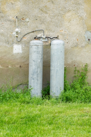 Gas bottles standing outside against a wall photo