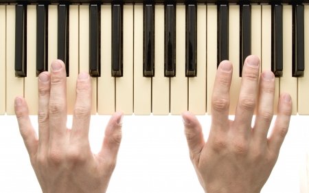 Piano keyboard with hands on white background photo