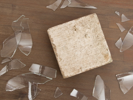 Brick with broken glass, violence concept, isolated on wood photo