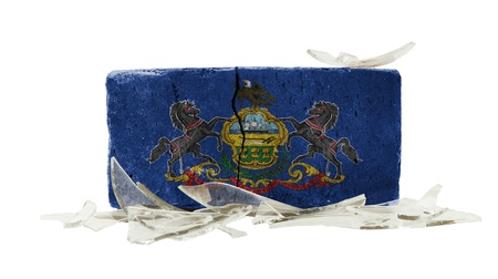 Brick with broken glass, violence concept, flag of Pennsylvania photo