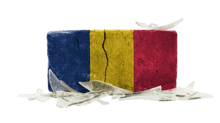 Brick with broken glass, violence concept, flag of Romania photo