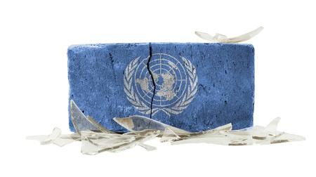 un: Brick with broken glass, violence concept, flag of the UN