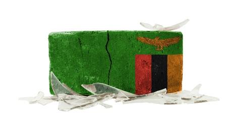 zambian: Brick with broken glass, violence concept, flag of Zambia Stock Photo