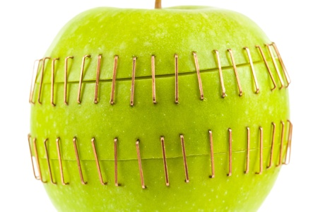 inverse: Sliced apple halves joined by brass staples