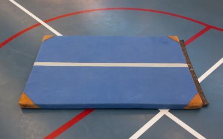 gymnastics sports: Very old blue mat on a blue court, school gym
