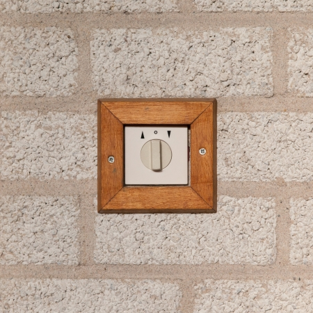 Old switch on a stone wall, isolated photo