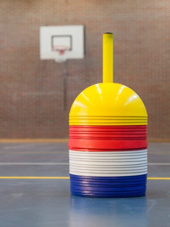 Interior of a gym at school, different colors of cones photo