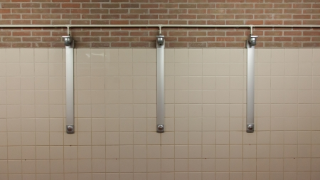 Three showers in a old bathroom interior photo