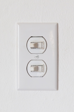 Close-up of an obsolete light-switches on a white wall photo