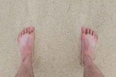 painted toenails: Fast wave comes in, feet standing still on a beach Stock Photo