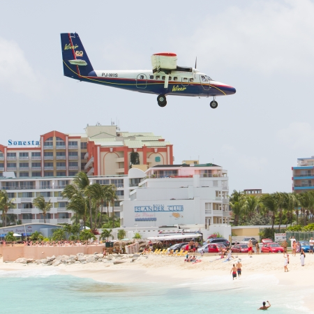 PRINCESS JULIANA AIRPORT, ST MAARTEN - July 19, 2013: Airplane lands over Maho beach on July 19, 2013. The 2300m runway is approached over the sea. ST MAARTEN, July 19, 2013