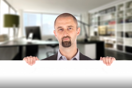 Businessman showing blank empty white billboard sign in his office photo