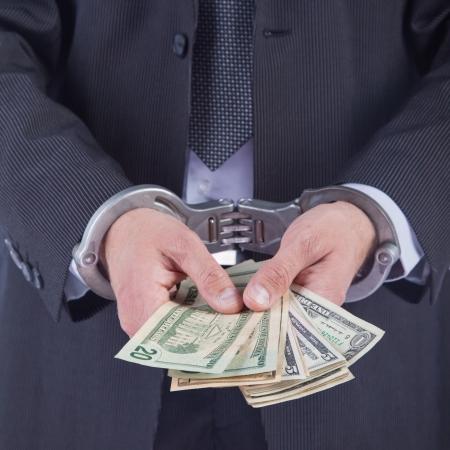 Homme d'affaires avec des menottes arrêté pour corruption, isolé sur blanc Banque d'images