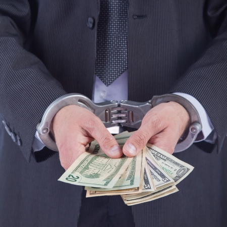 Business man in handcuffs arrested for bribe, isolated on white