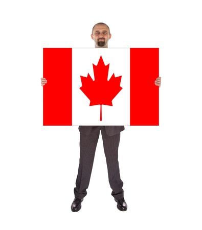 Smiling businessman holding a big card, flag of Canada, isolated on white photo