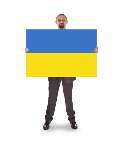 Smiling businessman holding a big card, flag of Ukraine, isolated on white photo
