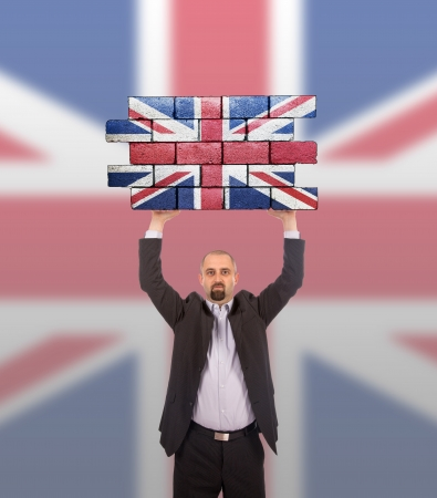 lifting jack: Businessman holding a large piece of a brick wall, flag of United Kingdom, isolated on national flag