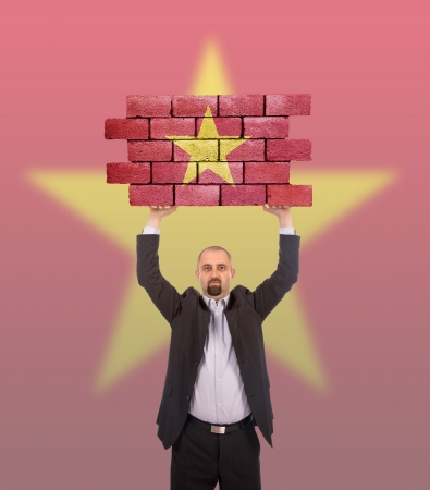 Businessman holding a large piece of a brick wall, flag of Vietnam, isolated on national flag photo
