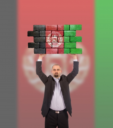 Businessman holding a large piece of a brick wall with flag of Afghanistan photo