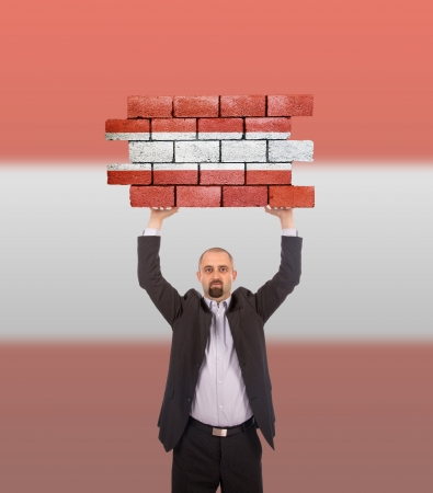 Businessman holding a large piece of a brick wall with flag of Austria photo
