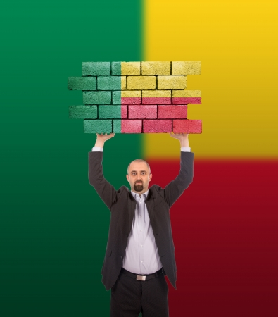 Businessman holding a large piece of a brick wall with flag of Benin