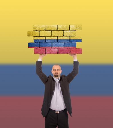 Businessman holding a large piece of a brick wall, flag of Colombia, isolated on national flag photo