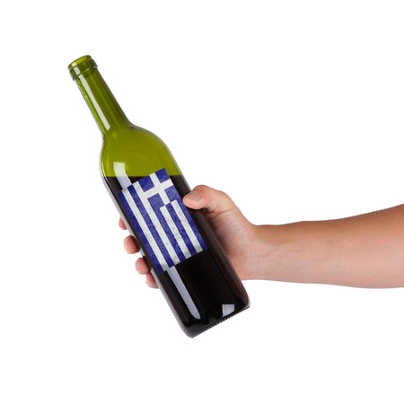 Hand holding a bottle of red wine, label of Greece, isolated on white, photo