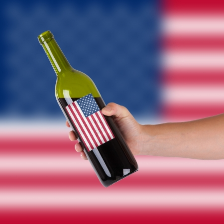 hand holding bottle: Hand holding a bottle of red wine, label of the United States, isolated on white,
