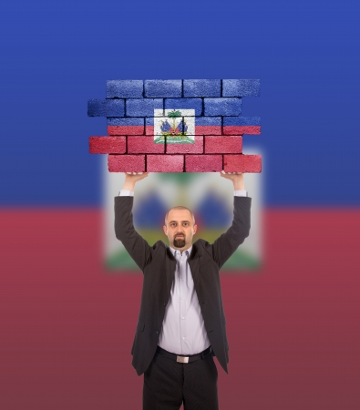 Businessman holding a large piece of a brick wall, flag of Haiti, isolated on national flag photo