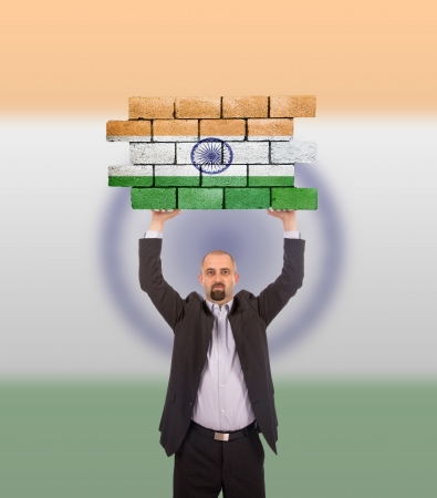 Businessman holding a large piece of a brick wall, flag of India, isolated on national flag photo