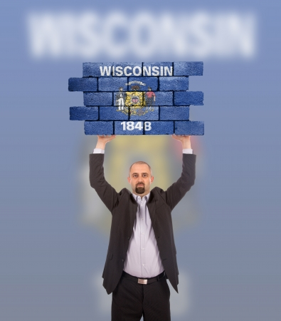 wisconsin flag: Businessman holding a large piece of a brick wall, flag of Wisconsin, isolated on national flag Stock Photo