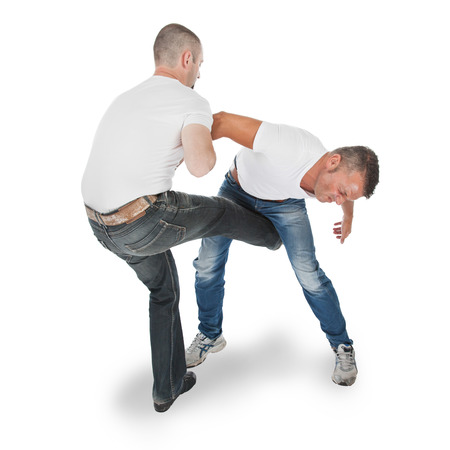 krav maga: Man defending an attack from another man, selfdefense, kicking in groin, isolated on white