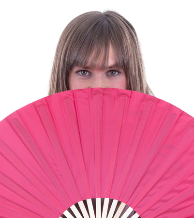 shyness: Studio portrait of a womans face partly hidden by a fan, isolated on white