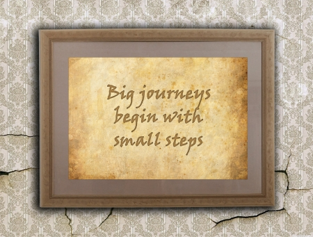Old wooden frame with written text on an old wall - Big journeys, small steps